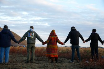 CANNON BALL, ND - NOVEMBER 24: Water protectors join hands in prayer at the end of the day's protest as police line the hill at Standing Rock on Nov. 24, 2016, during an ongoing dispute over the building of the Dakota Access Pipeline. (Photo by Jessica Rinaldi/The Boston Globe via Getty Images)
